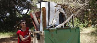 Una voluntaria empuja un contenedor lleno de residuos recogidos durante la mañana.  MOISES COPA
