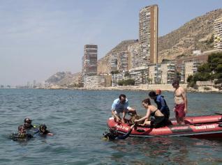 Los buzos extraen residuos del fondo del mar y los depositan en lanchas, en unos trabajos de limpieza realizados frente a la playa de la Almadraba y la Albufereta.  david costa