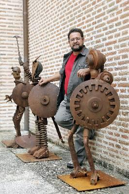 El abulense Juan Jesus Villaverde posa junto a algunas de sus esculturas realizadas con hierro procedente de piezas vinculadas a la actividad agricola y ganadera, y que pueden verse en el Castillo de Arevalo hasta el proximo mes de julio.EFE
